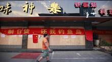 A man walks past a Chinese national flag and a banner covering the entrance to a Japanese restaurant in Suzhou, Jiangsu province, September 17, 2012. Major Japanese firms have shut factories in China and urged expatriate workers on Monday to stay indoors ahead of what could be more angry protests over a territorial dispute that threatens to hurt trade ties between Asia's two biggest economies. (ALY SONG/REUTERS)