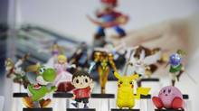 "Amiibo characters for Wii U are on display at the Nintendo booth during the Electronic Entertainment Expo, in Los Angeles on June 10, 2014. Pikachu and Link will be among the first characters coming to ""amiibo."" Nintendo announced the 12 characters on Friday, Aug. 29, 2014, that will be part of its upcoming toys-meet-game franchise set for release later this year. (JAE C. HONG/THE ASSOCIATED PRESS)"
