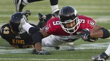 Calgary Stampeders' Jon Cornish dives for a first down away from Hamilton Tiger-Cats defender Neil King in the first half of their CFL football game in Guelph, Ontario September 28, 2013. (FRED THORNHILL/REUTERS)
