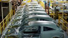 A row of car frames await their engines and interiors. (MICHEL WIEGANDT/AFP/Getty Images)
