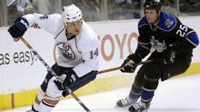 Edmonton Oilers' Raffi Torres, left, looks for an open teammate while being pursued by Los Angeles Kings' Jon Klemm during the first period of an NHL hockey game in Los Angeles, Monday, Dec. 3, 2007. (Chris Pizzello)