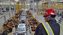 An employee looks at an assembly line at a Ford manufacturing plant in Chongqing municipality in this April 20, 2012 file photo. (SHI TOU/REUTERS)