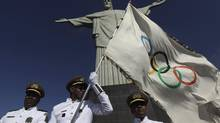 Municipal guards hold the Olympic Flag in front of the Christ the Redeemer statue in Rio de Janeiro Aug. 19, 2012. The city is hosting the 2014 World Cup as well as the 2016 Olympics. (RICARDO MORAES/REUTERS)
