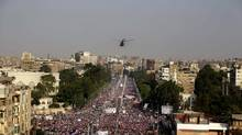 A military helicopter flies over the presidential palace as opponents of Egypt's Islamist President Mohammed Morsi protest in Cairo. (Hassan Ammar/AP)