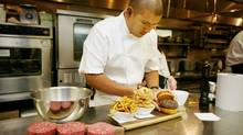 Chef David Lee in Nota Bene with a Stilton brisket beef burger with fois gras, pommes frites, and onion rings. (Charla Jones)