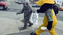 Emily Lavender, an activist with People for the Ethical Treatment of Animals, is chased by an unidentified man dressed in a dog suit in St. John's on Friday, Jan. 29, 2010. (ANDREW VAUGHAN)