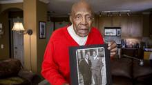 Following in the footsteps of Herb Trawick, Anderson was among the first African-American players in the CFL. He is seen holding a photo of him and Jackie Robinson taken in 1955 at the Royalite Service Station, which Anderson owned at the time in Calgary. (Chris Bolin For The Globe and Mail)