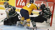 London Knights' Jarred Tinordi (R) is pushed into the net by Shawinigan Cataractes Felix-Antoine Bergeron (C) during the second period of their round-robin Memorial Cup ice hockey game in Shawinigan, Quebec, May 20, 2012. REUTERS/Mathieu Belanger (Mathieu Belanger/Reuters)