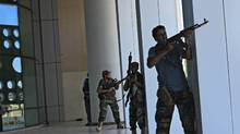 Rebel fighters take shelter as an intense gunbattle erupted outside the Corinthia hotel, where many foreign journalists are staying, in Tripoli, LIbya, Thursday, Aug. 25, 2011. (AP/Sergey Ponomarev/AP/Sergey Ponomarev)