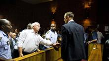 "South African ""Blade Runner"" Oscar Pistorius (R) talks to his father Henke after his court appearance in Pretoria February 15, 2013. Pistorius, a double amputee who became one of the biggest names in world athletics, broke down in tears on Friday after he was charged in court with shooting dead his girlfriend, 30-year-old model Reeva Steenkamp, in his Pretoria house. (Reuters)"