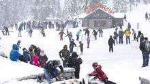 The skating pond atop Grouse Mountain is filled with people as snow billows down on top of the mountain on December 20, 2010, Vancouver. (Brett Beadle for The Globe and Mail/Brett Beadle for The Globe and Mail)