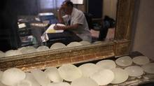 Defective silicone gel breast implants, which were removed from patients and manufactured by French company Poly Implant Prothese (PIP),are seen in the office of plastic surgeon Denis Boucq ,in background, in Nice, south eastern France. (Lionel Cironneau/AP)