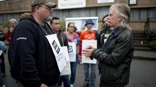 B.C. Teachers' Federation president Jim Iker, right, talks to striking teachers outside Britannia Secondary and Elementary schools in Vancouver on Sept. 2, 2014. (Jonathan Hayward/The Canadian Press)