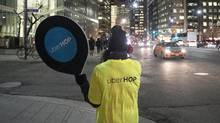 An Uber representative advertises free cab rides as part of a promotion to launch the Uber Hop service on Dec. 15, 2015. (File) (Chris Young For The Globe and Mail)