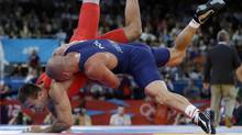 In this Monday, Aug. 6, 2012 file photo Amer Hrustanovic of Austria competes against Damian Janikowski of Poland, in blue, during the 84-kg Greco-Roman wrestling competition at the 2012 Summer Olympics, in London. (Associated Press)