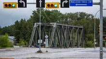 A river breaks its banks and flows over the main bridge in downtown High River, Alta. (CHRIS BOLIN FOR THE GLOBE AND MAIL)