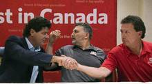 Unifor national president Jerry Dias, left, shakes hands with bargaining committee member Chris Taylor, right, of Ford Motors, after the conclusion of a news conference in Tornoto on Aug. 11. (Nathan Denette/THE CANADIAN PRESS)