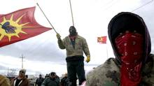 Native protesters stand at a housing development near Caledonia, Ont., despite a court order asking them to leave, on March 22, 2006. (Sheryl Nadler/The Canadian Press)