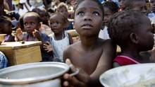 Children eat at a food distribution point at a makeshift camp in Jacmel. (MARCO DORMINO)
