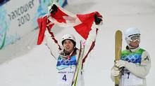 Alexandre Bilodeau of Quebec celebrates winning the gold medal in Freestyle Skiing Men's Moguls while silver medalist Dale Begg-Smith of Australia looks on dejected. (Streeter Lecka/Getty Images)