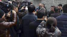 Chinese President Xi Jinping, middle, is surrounded by onlookers and television crew during an unannounced visit to a residential alley in Beijing, China Tuesday Feb. 25, 2014. Braving Beijing's choking smog, the president chatted with residents in his latest public relations effort. (The Associated Press)