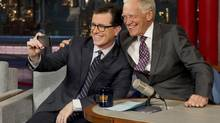 In this photo provided by CBS, Comedy Centrals Stephen Colbert, left, takes a selfie with host David Letterman on the set of the Late Show with David Letterman, Tuesday, April 22, 2014 in New York. (Jeffery R. Staab/AP)