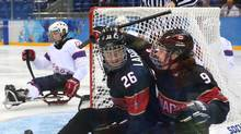 Dominic Larocque, left, and Anthony Gale of Canada celebrate a goal against Norway during their ice sledge hockey match in Sochi on Sunday. (SERGEI CHIRIKOV/EPA)