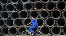 A labourer cycles past coils of steel wire at a steel wholesale market in Shenyang, Liaoning province in this file photo. (SHENG LI/REUTERS)