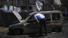 An Israeli man looks at a burnt car parked beside a paint factory in the southern Israeli town of Sderot June 29. (AMIR COHEN/REUTERS)