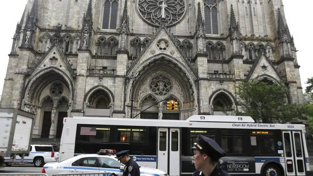 New York Police officers arrange barricades across the street from Cathedral Church of Saint John the Divine before funeral services for actor James Gandolfini. (Julio Cortez/AP)