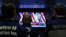 Traders watch as Hillary Clinton addresses her staff and supporters about the results of the U.S. election, on the floor of the New York Stock Exchange (NYSE) the morning after the U.S. presidential election in Nov. 9. (BRENDAN MCDERMID/REUTERS)