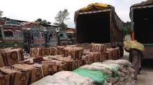 Boxes of bananas and sacks of tamarind are unloaded from trucks that arrived at this trade terminal on the Pakistan controlled of Kashmir after crossing the Line of Control. The trucks will return to the Indian-controlled side, where they came from, later in the day. (Affan Chowdhry/The Globe and Mail)