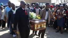 Mourners carry the casket of Andries Motlapula Ntsenyeho, one of the 34 striking platinum miners shot dead at Lonmin's Marikana mine in South Africa's Free State province, September 1, 2012. (MIKE HUTCHINGS/REUTERS)