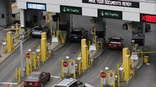 Vehicles crossing the border tunnel from Windsor, Ont., stop at U.S. custom booths in downtown Detroit in this photo from March 1, 2013. (REBECCA COOK/REUTERS)