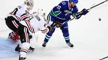 Vancouver Canucks forward Daniel Sedin (22) tries to knock down a high puck in front of the net of Chicago Blackhawks goaltender Corey Crawford (50) during the first period at Rogers Arena. (ANNE-MARIE SORVIN/USA TODAY SPORTS)