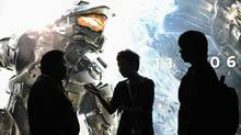 "Attendees hold a discussion in front of a banner for the new ""Halo 4"", during the Electronic Entertainment Expo (E3) in Los Angeles, California June 6, 2012. (GUS RUELAS/REUTERS)"