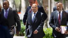 This file photo taken on February 24, 2016 shows South Africa's Minister of Finance Pravin Gordhan (C), walking out from the Finance Ministry with officials up to the South African Parliament to deliver the 2016 Budget Speech, in Cape Town. South African Finance Minister Pravin Gordhan will be prosecuted for fraud over alleged misconduct when he was head of the South African Revenue Service (SARS), officials said on October 11, 2016, in a move set to shake the country's fragile economy. (RODGER BOSCH/AFP/Getty Images)