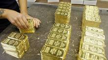 File photo of an employee preparing gold bars for transport at a plant of gold refiner and bar manufacturer Argor-Heraeus SA in the southern Swiss town of Mendrisio.) (ARND WIEGMANN/REUTERS)