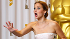 Jennifer Lawrence, best actress winner for her role in Silver Linings Playbook, reacts after photographers made a picture of her making an obscene gesture as she took the stage in the photo room with her Oscar at the 85th Academy Awards in Hollywood, California February 24, 2013.