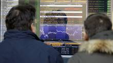 Two men check a monitor displaying the stock exchange index in Milan, Italy, Wednesday, Dec. 28, 2011. (Luca Bruno/Luca Bruno/AP)