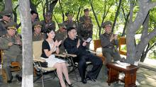 Ri Sol-ju carried the expensive purse on a trip to an army unit with her husband, North Korean leader Kim Jong-un, seen in this undated picture released by the North's official news agency in Pyongyang on Aug. 7, 2012. (KCNA/REUTERS)
