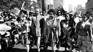 Winnie Mandela and Foreign Affairs Minister Joe Clark lead an anti-apartheid parade up University Avenue in Toronto on June 19, 1990.