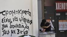 A couple hug in front of a shuttered shop in Thessaloniki, Greece. The partially obscured slogan, in Greek, reads 'Terrorism is to be looking for work, and to live with peanuts.' (Nikolas Giakoumidis/AP/Nikolas Giakoumidis/AP)