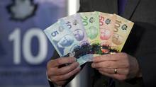 The polymer bank notes are pictured at the central train station in Vancouver, Thursday, Nov. 7, 2013. (JONATHAN HAYWARD/THE CANADIAN PRESS)