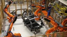 A worker makes technical measurements with robots on the carbon chassis at the serial production BMW i3 electric car in the BMW factory in Leipzig September 18, 2013. (FABRIZIO BENSCH/REUTERS)