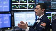 Traders applaud on the floor of the New York Stock Exchange (NYSE) as members of the New York Fire Department enter to ring the closing bell, March 31. (Drew Angerer/Getty Images)