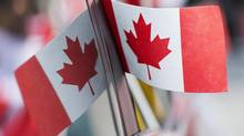 A Canadian flag is reflected in a car window during the annual Canada Day parade in Montreal, Tuesday, July 1, 2014. (Graham Hughes/THE CANADIAN PRESS)