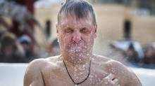 A Russian Orthodox worshiper plunges into a pool of ice water in celebration of Epiphany in Moscow's Red Square, January 19, 2014. (John Lehmann/The Globe and Mail)