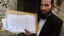 In this Wednesday, May 28, 2014 file photo, Mustafa Kharal, a lawyer for Farzana Parveen, 25, who was stoned to death, shows her marriage certificate in Lahore, Pakistan. The father of a pregnant Pakistani woman who was stoned to death and four other men have been charged with killing her after she married against the family's wishes and their trial was set to begin on Monday, police said. (K.M. Chaudary/AP)