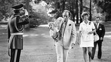 Pierre Elliott Trudeau, carrying young Justin under his arm like a football, while at left an RCMP officer performs a smart salute. (Peter Bregg)